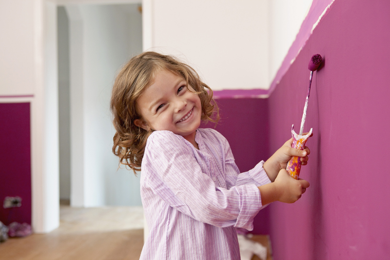 Little girl painting her room magenta and pink