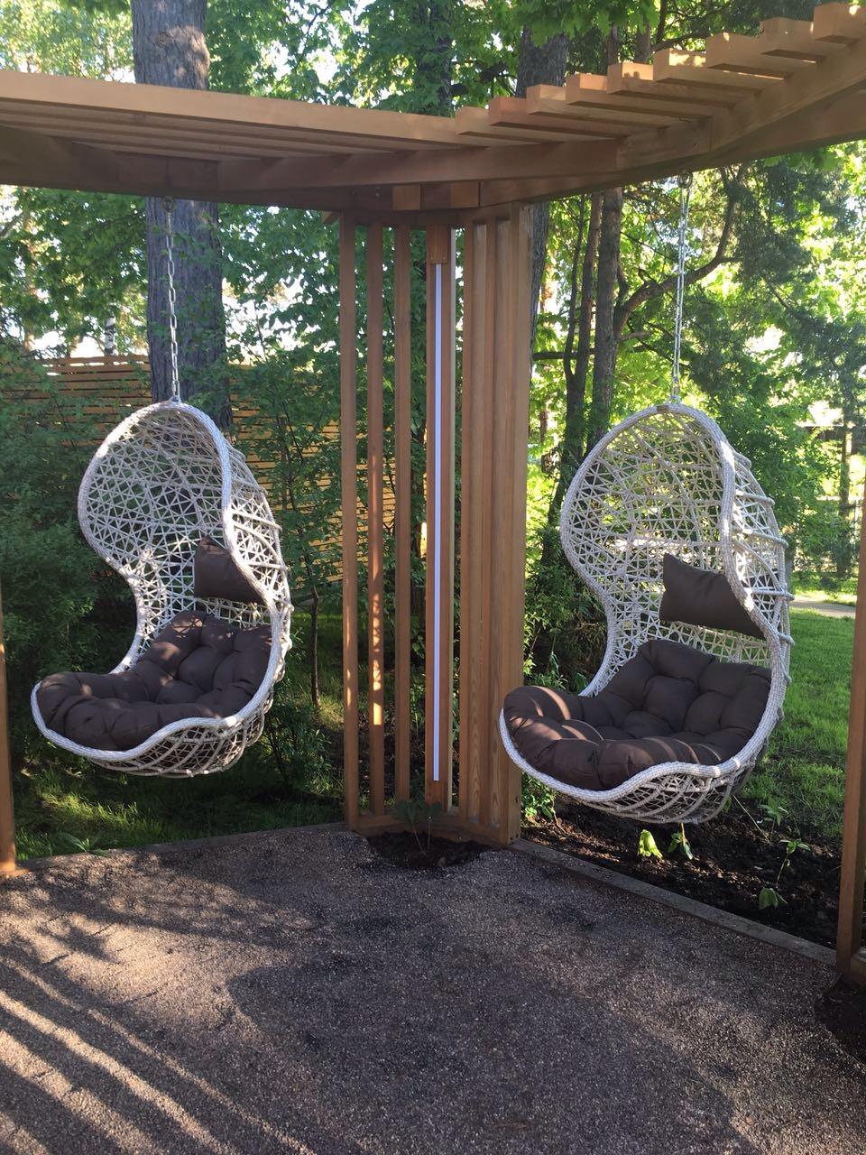 подвесное кресло из искусственного ротанга в саду